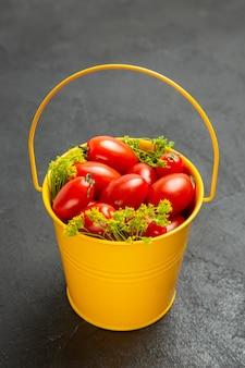Vista inferior do balde de tomates cereja e flores de endro em fundo escuro