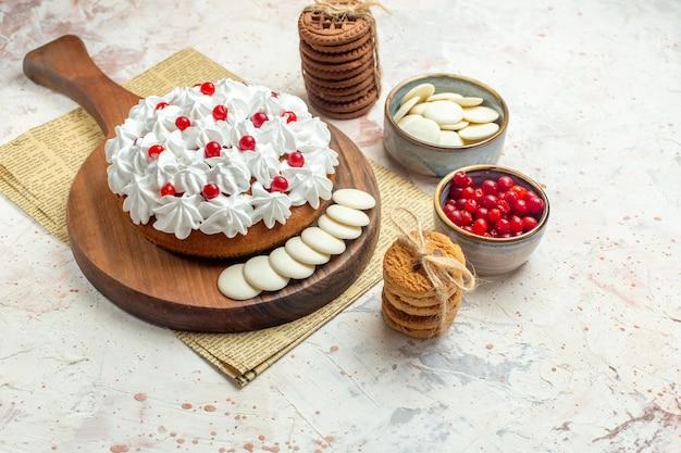 Vista inferior do bolo com creme de confeiteiro branco na placa de madeira em frutas de jornal e chocolate branco em bolachas amarradas com corda na superfície cinza claro