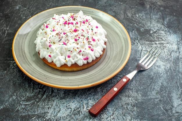 Vista inferior do bolo com creme de confeiteiro branco no garfo de prato redondo cinza na mesa cinza