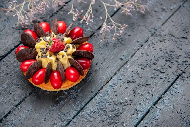 Vista inferior do bolo com fruta cornel, framboesa e chocolate no fundo escuro de madeira