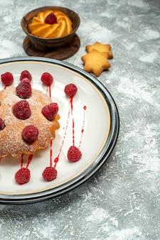 Vista inferior do bolo de frutas vermelhas em um biscoito de prato oval branco em uma tigela na superfície cinza