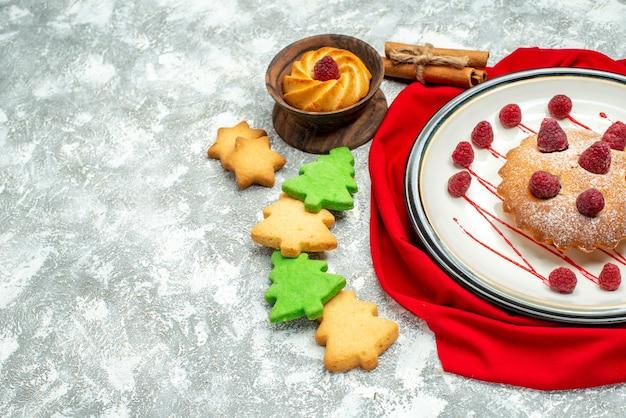Vista inferior do bolo de frutas vermelhas em um prato oval branco biscoitos de xale vermelho em um espaço livre de superfície cinza