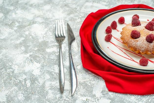 Vista inferior do bolo de frutas vermelhas em um prato oval branco, garfo de xale vermelho e faca de jantar em um espaço livre de superfície cinza