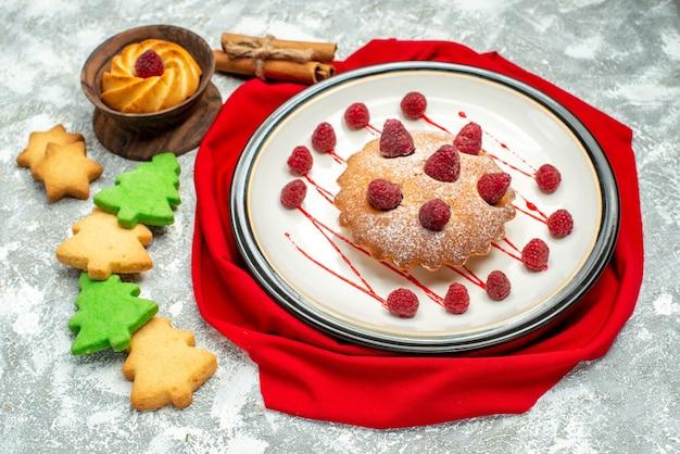 Vista inferior do bolo de frutas vermelhas em um prato oval branco xale vermelho biscoitos de árvore de natal na superfície cinza