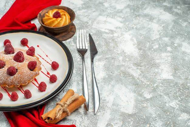 Vista inferior do bolo de frutas vermelhas em uma placa oval branca xale vermelho garfo de biscoito e canela em bastões de canela na superfície cinza com espaço de cópia