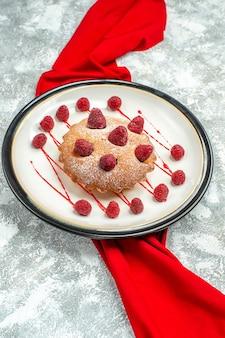 Vista inferior do bolo de frutas vermelhas em uma placa oval branca xale vermelho na superfície cinza