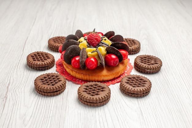 Vista inferior do bolo de frutas vermelhas no guardanapo de renda oval vermelha e biscoitos na mesa de madeira branca