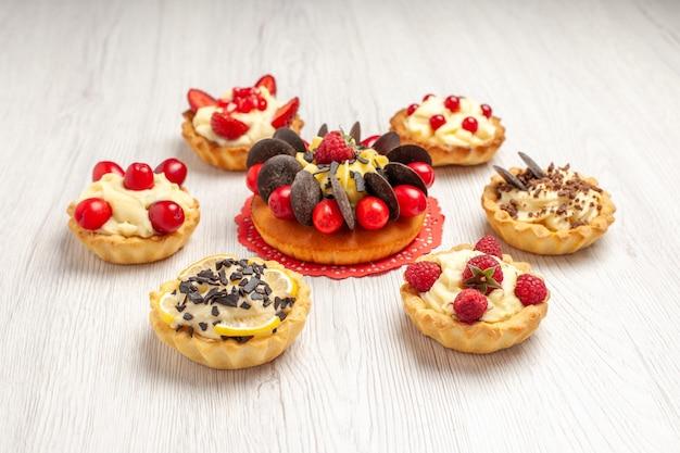 Vista inferior do bolo de frutas vermelhas sobre o guardanapo de renda oval vermelha arredondado com tortas no fundo branco de madeira
