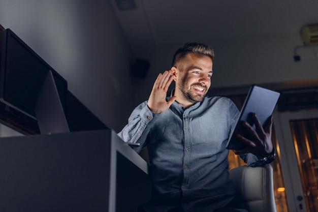 Vista inferior do bonito freelancer barbudo caucasiano com sorriso, sentado no escritório tarde da noite e usando o tablet para vídeo chamada.