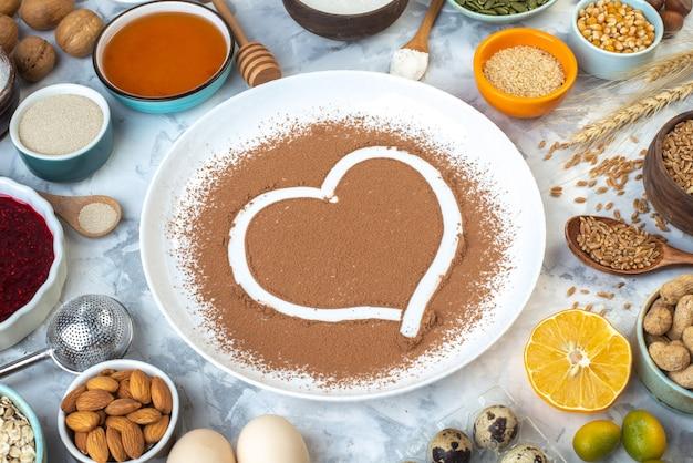 Vista inferior do coração impresso em cacau em pó outros produtos em tigelas ovos nozes na mesa