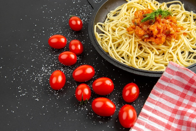 Vista inferior do espaguete com molho na frigideira, tomate cereja na mesa preta