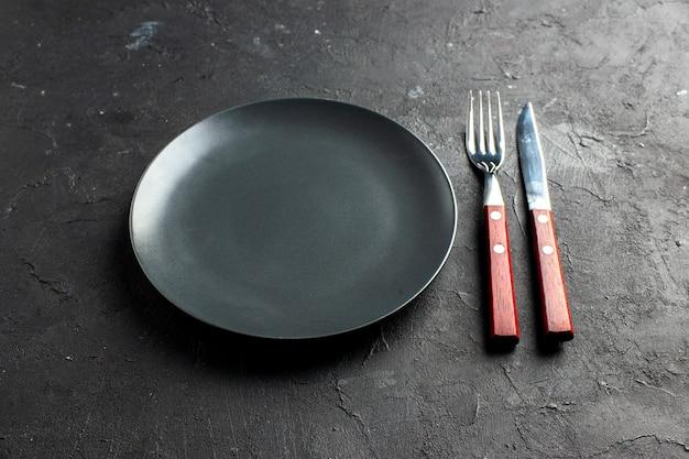 Vista inferior do prato redondo preto, um garfo e uma faca na superfície preta