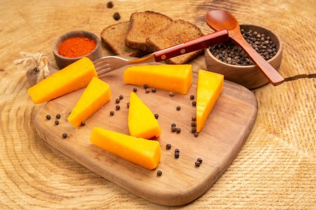 Vista inferior do queijo nas fatias do garfo de queijo na tábua de cortar fatias de pimenta preta de pão na mesa de madeira