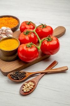 Vista inferior do ramo de tomate fresco cúrcuma de alho na tábua de cortar colheres de madeira com pimenta preta e feijão na mesa cinza