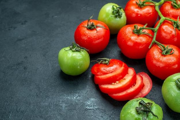 Vista inferior do ramo de tomate picado tomate verde fresco na mesa preta lugar grátis