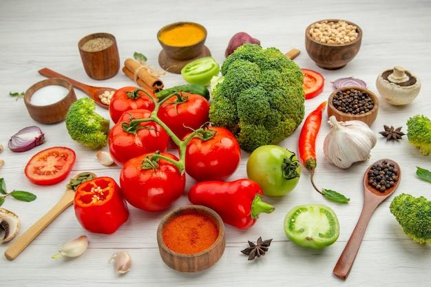 Vista inferior do ramo de tomate taças com diferentes feijões e especiarias, brócolis, colheres de madeira e alho na mesa cinza