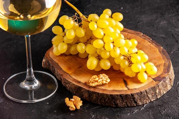 Vista inferior do vinho branco em vidro de uvas amarelas na placa de madeira na mesa escura