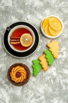 Vista inferior dos biscoitos da árvore de natal, uma xícara de chá com fatias de limão na superfície cinza