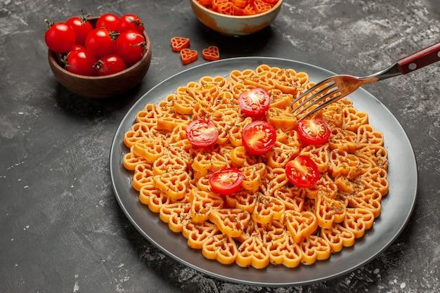 Vista inferior dos corações de massa italiana cortam tomate cereja no prato, garfo, tomate cereja e macarrão coração em uma tigela na mesa cinza