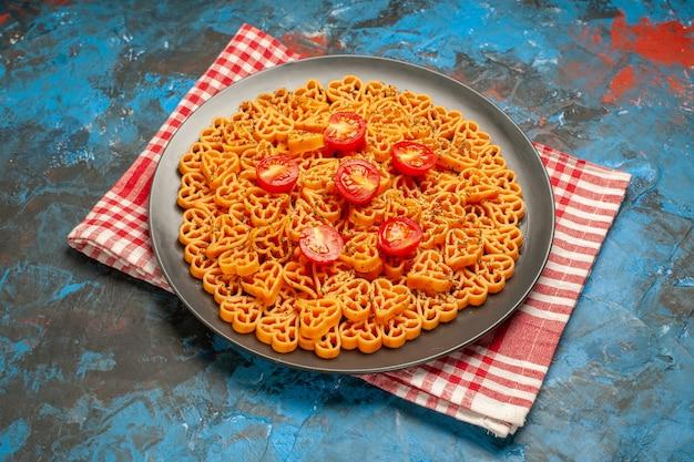 Vista inferior dos corações de massa italiana cortam tomates cereja no prato, na toalha de cozinha quadriculada branca vermelha na mesa azul