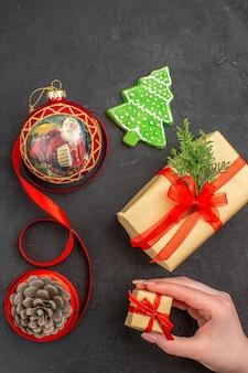 Vista inferior dos presentes de natal em fita de papel pardo, brinquedo de árvore de natal no jornal em fundo escuro