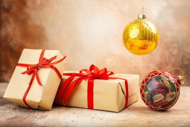Vista inferior dos presentes de natal em fita de papel pardo, brinquedo de árvore de natal no jornal no escuro