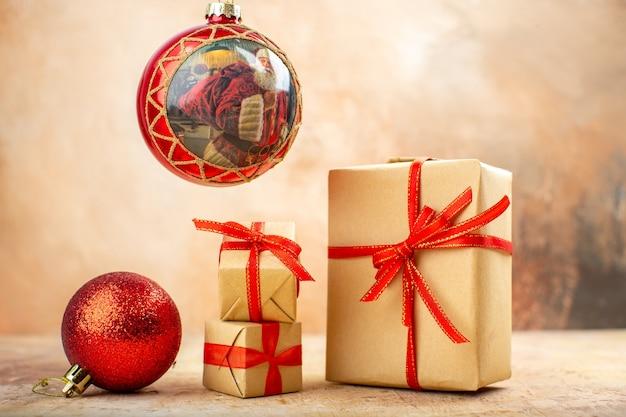 Vista inferior dos presentes de natal em fita de papel pardo, brinquedos para árvore de natal em jornal em bege