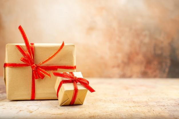Vista inferior dos presentes de natal em fita de papel pardo, brinquedos para árvore de natal no jornal em fundo bege