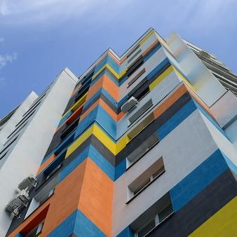 Vista inferior edifício residencial colorido e céu azul
