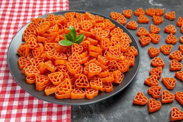 Vista inferior em forma de coração com macarrão vermelho italiano em prato preto oval no pano de prato macarrão com coração espalhado na mesa escura