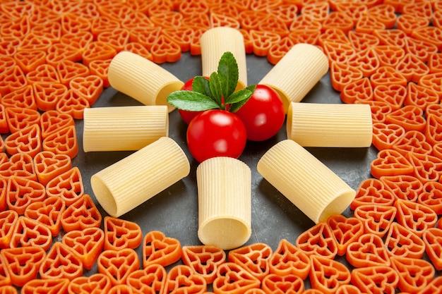 Vista inferior em forma de coração, macarrão italiano rigatoni e tomate cereja em superfície escura