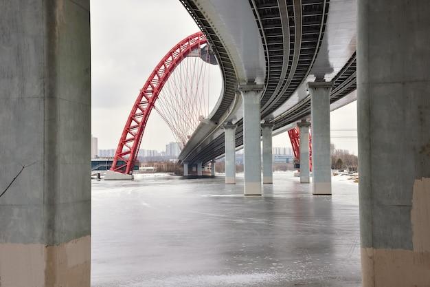 Vista inferior entre pilares de concreto na ponte rodoviária com um arco vermelho, a ponte pitoresca sobre o rio moscou