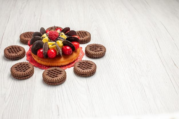 Vista inferior esquerda do bolo de frutas vermelhas sobre o guardanapo de renda oval vermelha arredondado com biscoitos na mesa de madeira branca com espaço livre