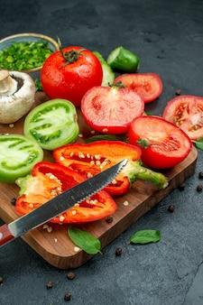 Vista inferior faca de pimentão tomate verde e vermelho de vegetais na tábua de cortar verdes em uma tigela na mesa preta