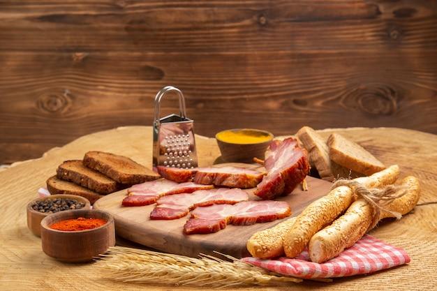 Vista inferior fatias de becon na placa de madeira caixa de pão branco e marrom especiarias ralador na mesa de madeira