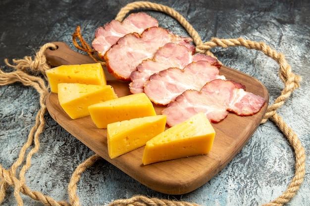 Vista inferior fatias de carne fatias de queijo na tábua de cortar em fundo cinza