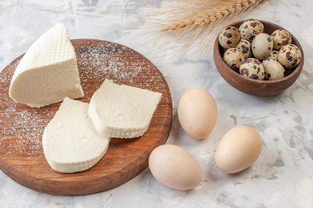 Vista inferior fatias de queijo branco na tábua de madeira ovos de galinha ovos de codorna em uma tigela espigas de trigo na mesa
