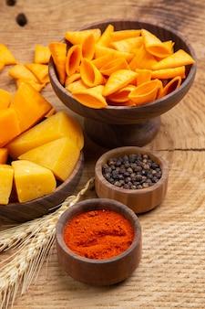 Vista inferior fatias de queijo em uma tigela pimenta preta pimenta vermelha em pó chips espiga de trigo na mesa de madeira