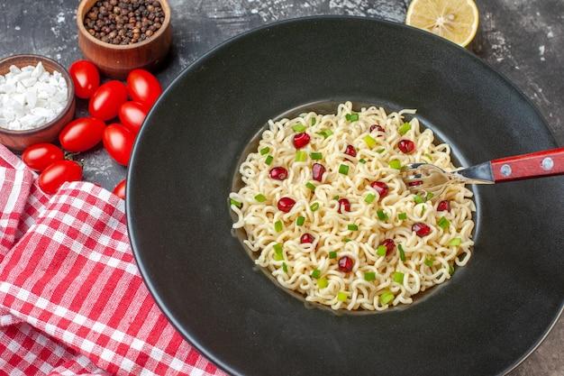 Vista inferior garfo de macarrão ramen asiático na placa preta corte limão, tomate cereja sal marinho pimenta preta em pequenas tigelas na mesa escura