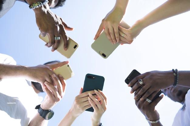 Vista inferior grupo diversificado de amigos com telefones