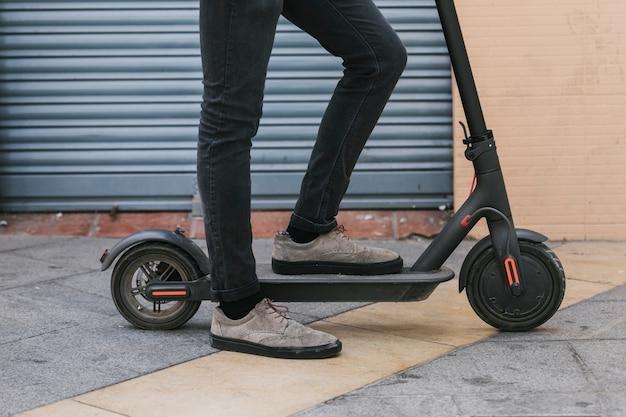 Vista inferior homem lateral descansando em e-scooter