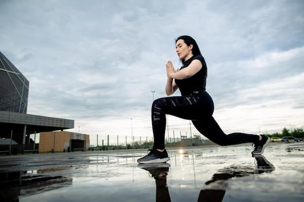 Vista inferior, jovem morena desportiva está treinando ao ar livre. mulher faz lunges ao ar livre. fitness, treino, conceito de desporto