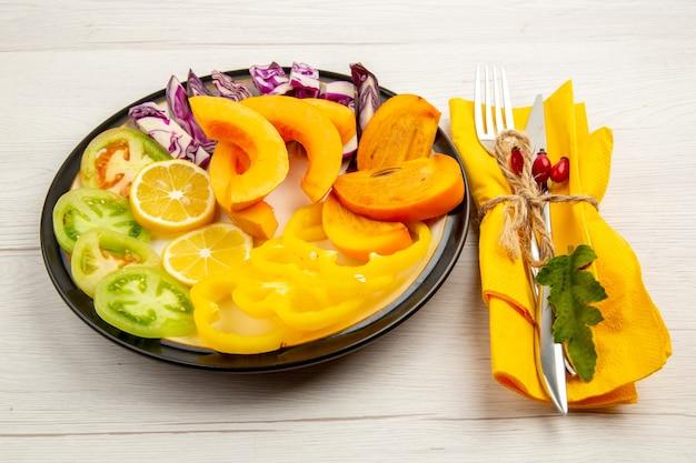 Vista inferior legumes e frutas picados abóbora pimentões caqui tomates verdes repolho roxo na placa preta garfo e faca no guardanapo amarelo na superfície branca