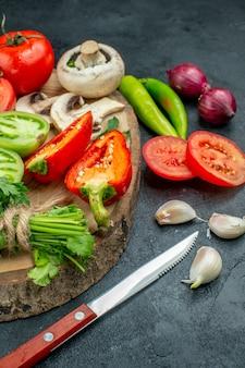 Vista inferior legumes frescos cogumelos tomates vermelhos e verdes pimentões verdes no tabuleiro rústico pimentas faca alho na mesa escura