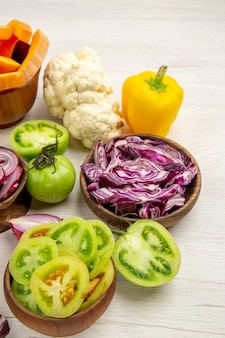 Vista inferior legumes frescos cortados tomates verdes cortados repolho roxo em tigelas couve-flor de pimentão na mesa de madeira branca