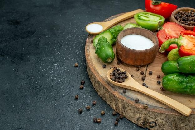 Vista inferior, legumes frescos pepinos pimenta preta e sal em colheres de madeira e tigelas tomate vermelho e verde pimentão na placa de madeira no espaço livre da mesa escura