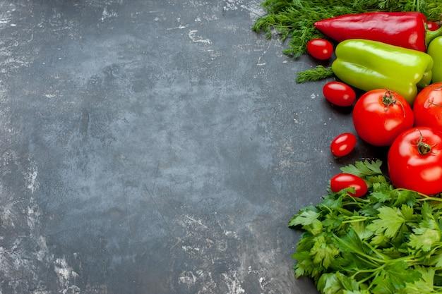 Vista inferior legumes frescos pimentões vermelhos e verdes tomates cereja salsa tomates em superfície escura com local de cópia
