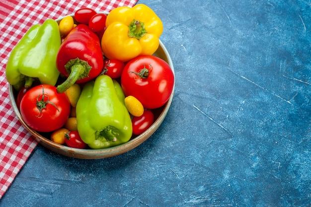 Vista inferior legumes frescos tomates cereja cores diferentes pimentões tomates cumcuat no prato na toalha de mesa quadriculada branca vermelha na mesa azul