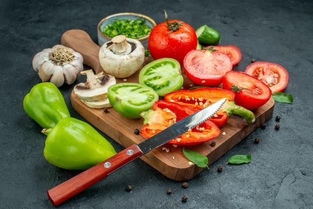 Vista inferior legumes pepinos tomates verdes e vermelhos faca pimentão na tábua de cortar alho verdes em uma tigela na mesa preta