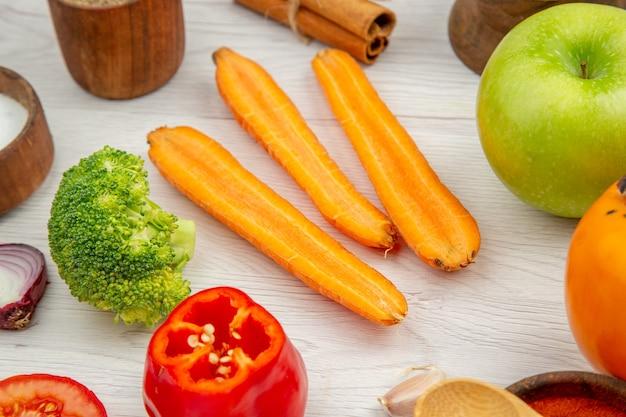Vista inferior legumes picados cenoura brócolis pimentão pimentão tigelas pequenas na mesa de madeira cinza